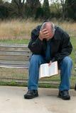 Bibbia triste della holding dell'uomo Fotografia Stock
