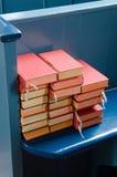 Bibbie su un banco di chiesa blu Fotografie Stock Libere da Diritti