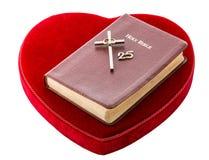 Bibel över röd sammethjärta Arkivfoton