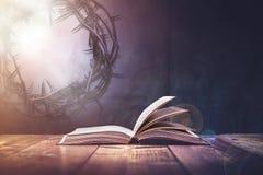 Bibel med ett ljus som kommer från över Arkivbilder