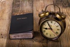 Bibel med klockan på trä Fotografering för Bildbyråer