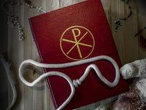 Bibel med radbandet och nalle arkivfoton