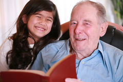 Bibel Messwert des älteren Mannes und des kleinen Mädchens zusammen Stockfotografie