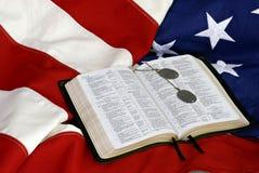 Bibel mit Hundeplaketten auf US-Markierungsfahne Stockbilder
