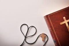 Bibel mit kreuzförmigem Anhänger und einem Herzen formte Schnur stockfotos