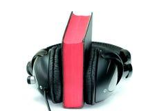 Bibel och hörlurar Arkivfoto