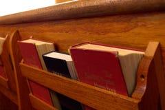 Bibel och psalmbok i kyrkbänk fotografering för bildbyråer
