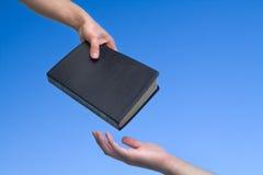 bibel som ger handen Arkivbilder