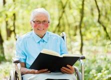 Bibel som läs av åldring i Wheechair Arkivfoton