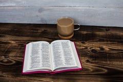 Bibel und Kaffee mit Milch auf hölzernem Hintergrund Stockfoto