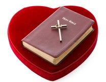 Bibeln och korsar över en röd sammethjärta Arkivfoto