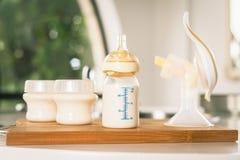 Biberón con leche y la bomba de lactancia manual Imagenes de archivo