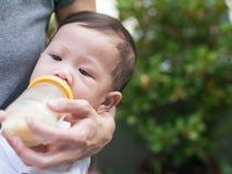 Biberon asiatico della madre il suo bambino in giardino Fotografia Stock