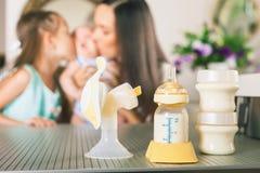 Biberon con il latte di madri e le tiralatte manuali Fotografia Stock