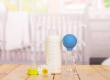 Biberon con latte ed il seno manuale sulla cucina del fondo Immagine Stock Libera da Diritti