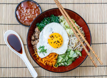 Bibimbap in a bowl with sauces on bamboo mat, korean dish Royalty Free Stock Image