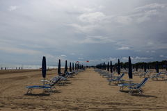 Bibione beach Italy with clear blue sky and sun umbrellas. Summer view of Bibione beach in North Italy Veneto with clear blue sky sun umbrellas and rescue boat Royalty Free Stock Photos