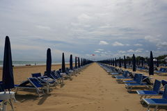 Bibione beach Italy with clear blue sky and sun umbrellas. Summer view of Bibione beach in North Italy Veneto with clear blue sky sun umbrellas and rescue boat Royalty Free Stock Images