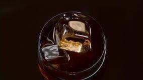 Bibita di Brown con ghiaccio in vetro Vista superiore stock footage