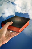 Bible. Mans hand is holding a bible, isolated on white background Stock Photos