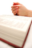 Bible. Praying hands on an open bible Stock Image