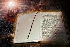 The Bible. A holy Bible on an old wooden table, lighted by a candle Royalty Free Stock Photos