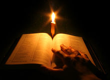 Bible. A bible open on a table next to a candle Stock Images