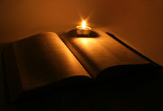 Bible. A bible open on a table next to a candle Stock Photo