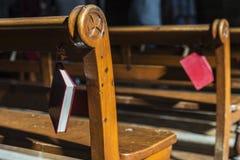 Bible accrochant sur un banc en bois à l'intérieur d'une église photos stock