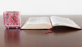 Bible and Alarm Clock on side Royalty Free Stock Image