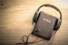Bible background. Holy Bible with headphones - symbol of listening to the Word of God Stock Photo