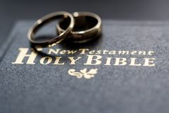 The bible is the base where upon two wedding rings rest. Wedding symbols, attributes. Holiday, celebration royalty free stock photo