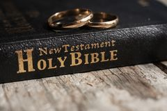 The bible is the base where upon two wedding rings rest. Wedding symbols, attributes. Holiday, celebration royalty free stock image