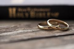 The bible is the base where upon two wedding rings rest. Wedding symbols, attributes. Holiday, celebration royalty free stock photography