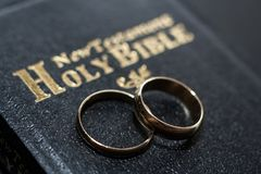 The bible is the base where upon two wedding rings rest. Wedding symbols, attributes. Holiday, celebration stock photography