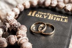 The bible is the base where upon two wedding rings rest. Wedding symbols, attributes. Holiday, celebration stock photos