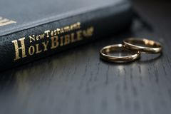 The bible is the base where upon two wedding rings rest. Wedding symbols, attributes. Holiday, celebration stock images