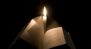 Bible book changes pages in front of a candle Royalty Free Stock Photos