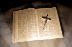 Bible book with crucifixion and shine over it. Stock Photography