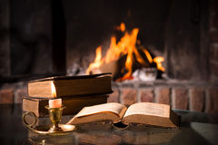 Bible with a burning candle. An open Bible with a burning candle in front of fireplace Royalty Free Stock Photo