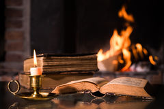 Bible with a burning candle. An open Bible with a burning candle in front of fireplace Stock Photography