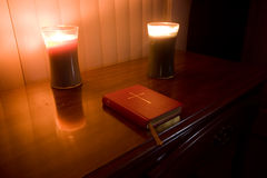 Bible and candle. Christian religious book and candles on table Royalty Free Stock Image