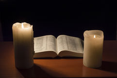 Bible with candlelight Stock Images