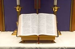 Bible and candles on altar. A view of an open holy Bible as it sits on a Protestant church altar with two candlesticks in the background Stock Image