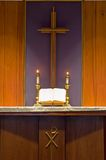 Bible and candles on altar. A view of an open holy Bible on a Protestant church altar with two burning candlesticks and a cross in the background Royalty Free Stock Photos