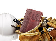 Bible and Carpenters Tool Belt with White Helmet Royalty Free Stock Images