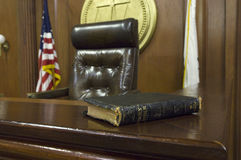 Bible And Chair In Courtroom. Holy Bible on table beside judge's chair in courtroom stock photo