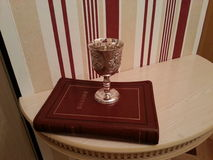 The Bible and the chalice for the Holy communion. A book of the Bible and a bowl for the remembrance on the table in the interior Royalty Free Stock Photo