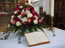 The Bible in the Church in front of a bouquet of flowers Royalty Free Stock Photos