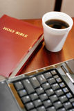 Bible and computer. Conceptual photo of a holy bible book next to a laptop computer keyboard and plastic cup of coffee stock image